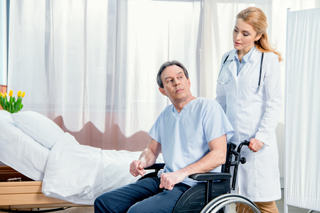 elderly man sitting in wheelchair and doctor standing near him