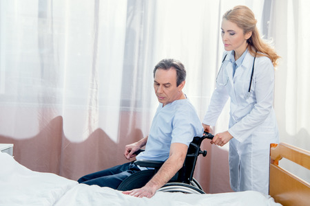 man sitting in wheelchair and doctor standing near him in hospital Stock Photo
