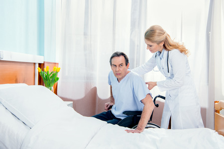 man sitting in wheelchair and doctor helping him in hospital Stock Photo