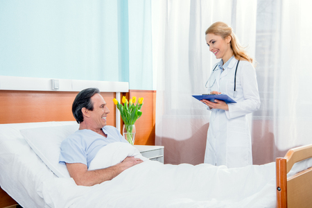 middle aged patient lying on bed and doctor with diagnosis standing near him