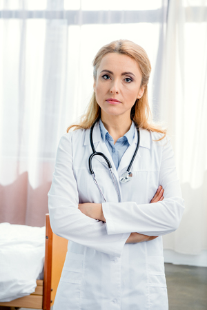 portrait of serious doctor with stethoscope standing with crossed arms Stock Photo