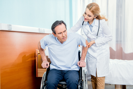 elderly man sitting in wheelchair and doctor helping him Stock Photo