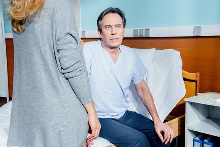 Mann , der auf Krankenhausbett mit Frau nahe sitzt Standard-Bild - 78111424