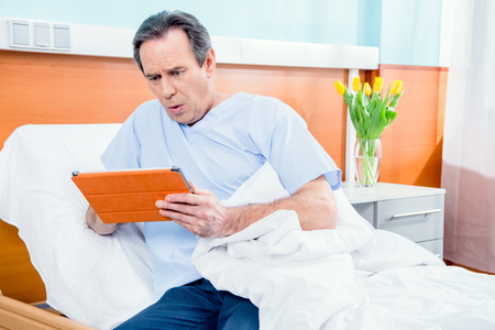 aged patient using digital tablet and sitting on bed in hospital