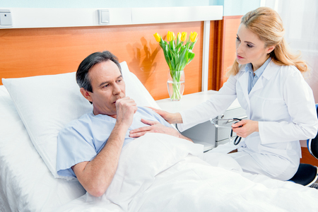 middle aged with chest pain lying on bed and doctor with stethoscope sitting near him Stock Photo