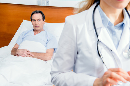 middle aged patient lying on bed and doctor standing in front Stock Photo