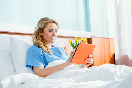 woman using digital tablet while lying in hospital bed Stock Photo