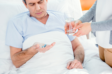 man taking medicines and woman holding glass of water