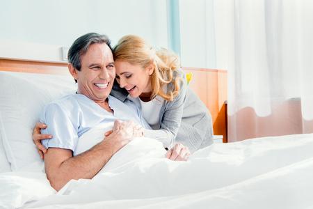 wife visiting smiling elderly husband in hospital