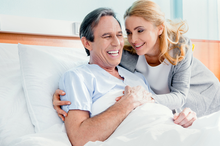 happy wife visiting elderly husband in hospital