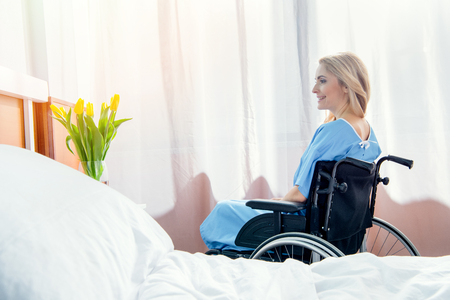 smiling wheelchair woman looking at tulips in hospital