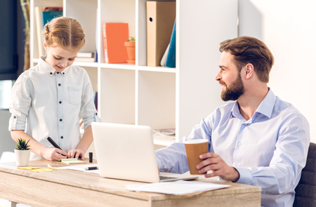 businessman working with laptop in office while his daughter drawing near Stock Photo