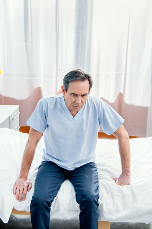 middle aged patient sitting on bed in chamber