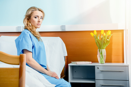 pensive woman sitting on hospital bed