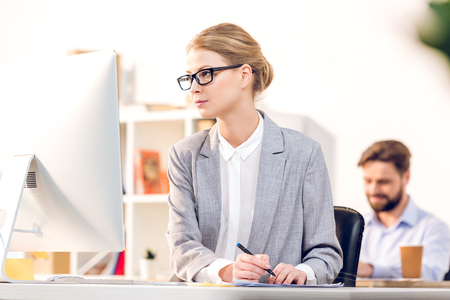 attractive businesswoman with eyeglasses using computer working in office Фото со стока