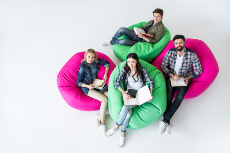 overhead view of students sitting on beanbag chairs and studying in studio