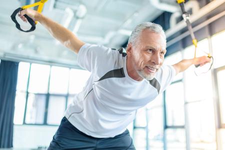 Sportman training met weerstand band in sportcentrum Stockfoto