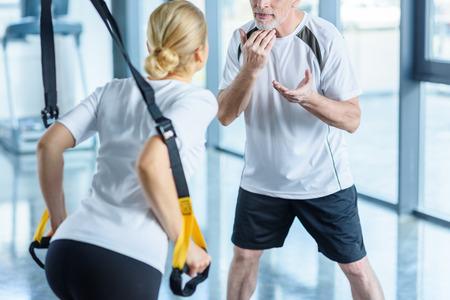 Sportswoman en senior trainer training met weerstand band