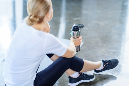 sportswoman holding sport bottle in sports center