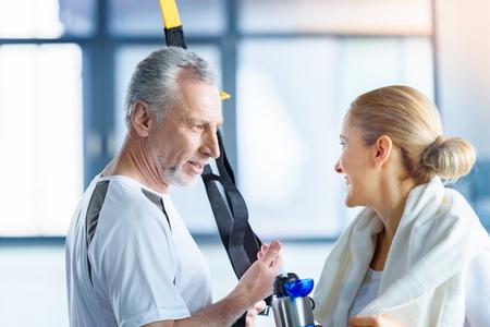 Sportvrouw met sportfles en senior sportman met weerstandspraat praten