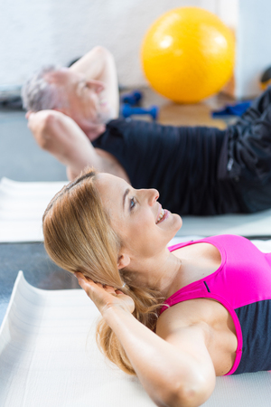 smiling man and woman in sportswear doing abs in gym