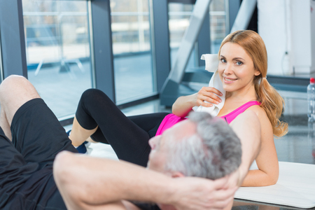blonde woman with towel looking at camera while mature man doing abs