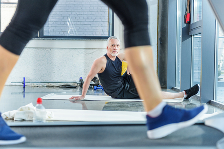 mature sportsman sitting on yoga mat and looking at woman training on treadmill Stock Photo