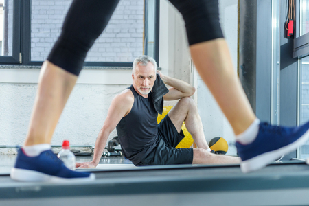 mature sportsman sitting on yoga mat with towel while woman training on treadmill