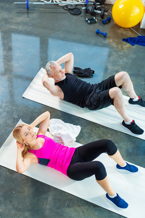 laying abs exercise: smiling man and woman in sportswear doing abs in gym