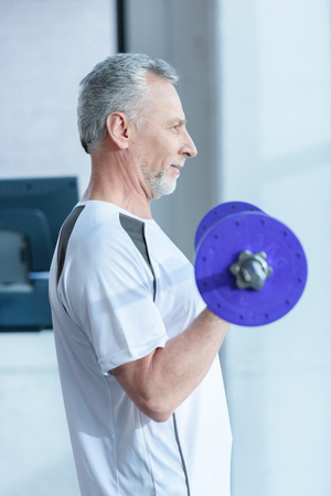 bearded mature sportsman training with barbell in gym