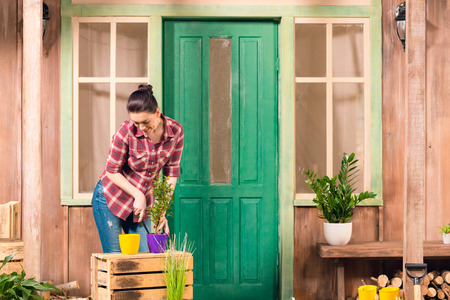 young woman cultivated plant in pot while standing on porch
