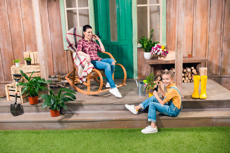 dungarees: mother sitting in rocking chair and smiling daughter cultivating plant on porch