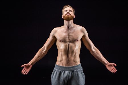 shirtless bearded bodybuilder posing isolated on black