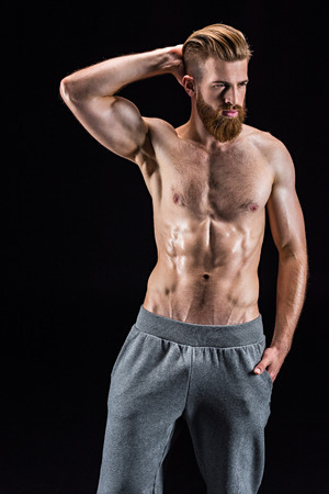 shirtless bearded bodybuilder posing isolated on black
