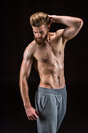 shirtless bebaarde bodybuilder poseren geïsoleerd op zwart