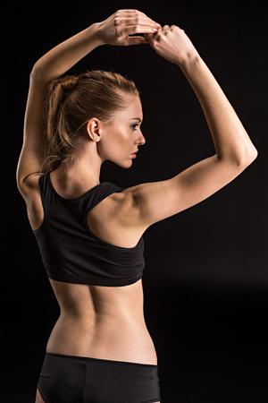 Sportvrouw in zwarte ondergoed geïsoleerd op zwart