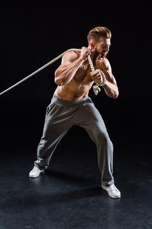 bearded sportman schreeuwen en trekken touw geïsoleerd op zwart Stockfoto