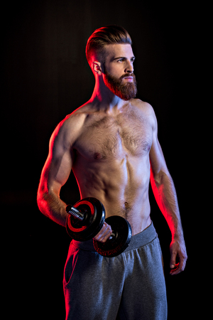bodybuilder training with dumbbell isolated on black with dramatic lighting