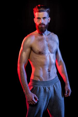 bodybuilder poseren geïsoleerd op zwart met dramatische belichting