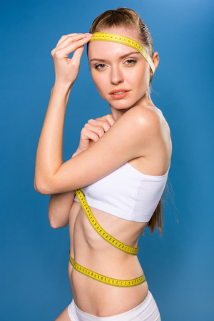 sportswoman in white underwear with measuring tape isolated on blue in studio