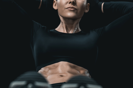 fitness woman doing abs on mat isolated on black. Stock Photo - 78286678