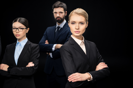 business team standing with crossed arms isolated on black Stock Photo