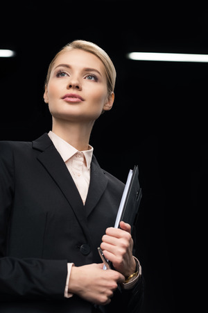 confident businesswoman with notepad in hand