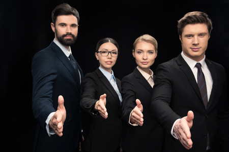 business team stretching out hands for shaking isolated on black