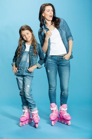 어머니와 딸이 롤러 스케이트, 스튜디오에서 엄지와 여자
