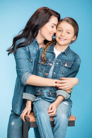 Joyeuse mère et fille étreintes en studio sur le bleu