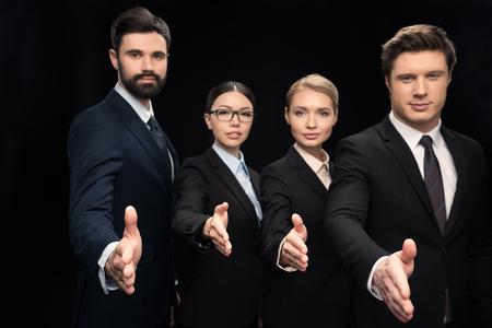 zakelijk team dat handen uitrekt voor het schudden geïsoleerd op zwarte, bedrijfsgroepswerkconcept Redactioneel