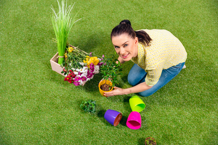 gardener with plants and flowerpots sitting on green grass