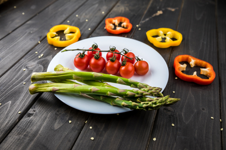 fresh seasonal vegetables on plate on wooden table background