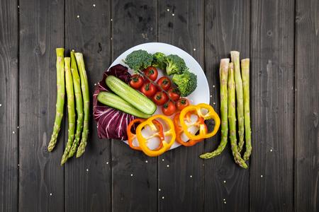 소박한 나무 배경에 접시에 신선한 야채